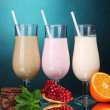 Milk shakes with fruits and chocolate on blue background - Stockfoto
