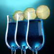 Blue cocktail in glasses with lime on blue background — Stock Photo