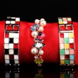 Three beautiful bracelets on the red cloth on black background — 图库照片
