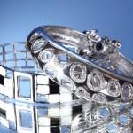 Beautiful silver bracelets on blue background — Stock Photo