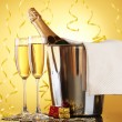 Champagne bottle in bucket with ice and glasses of champagne, on yellow background — Stock Photo #10587142