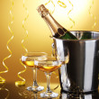 Champagne bottle in bucket with ice and glasses of champagne, on yellow background — Stock Photo #10587239