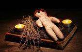 Dziewczyna lalki voodoo na drewnianym stole w blasku świec — Zdjęcie stockowe