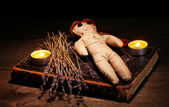 Voodoo doll girl on a wooden table in the candlelight — Stok fotoğraf