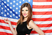 Beautiful young woman with the American flag on the background — Stok fotoğraf