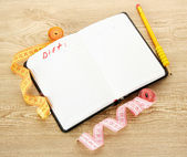 Planning of diet. Notebook measuring tapes and pen on wooden table — Stock Photo