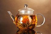 与异国情调绿茶棕色背景上的木桌上的玻璃茶壶 — 图库照片