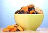 Sušené ovoce v zelené prohlubni na dřevěný stůl na modrém pozadí — Stock fotografie