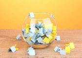 Pieces of paper for lottery in vase on wooden table on yellow background — Stock Photo