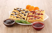Sweet waffles with jam and chocolate on plate on wooden background — Fotografia Stock