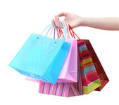 Female hand holding bright shopping bags isolated on white — Stock Photo