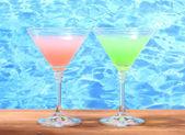Bicchieri di cocktail sul tavolo di legno su sfondo azzurro del mare — Foto Stock