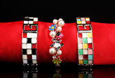 Three beautiful bracelets on the red cloth on black background — Стоковое фото