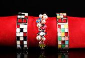 Tre braccialetti bellissime sul panno rosso su sfondo nero — Foto Stock