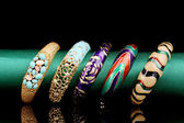 Five beautiful bracelets on the green cloth on black background — Stock Photo