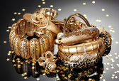 Beautiful golden jewelry on grey background — Stock Photo