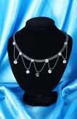 Beautiful silver necklace on mannequin on blue silk fabric — Stock Photo