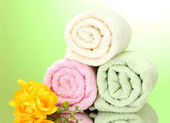 Colorful towels and flowers on green yellow background — Stock Photo