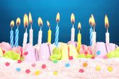 Birthday cake with candles on blue background — Stock Photo