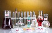 Tubos de ensaio com vários ácidos e produtos químicos no fundo brilhante — Foto Stock