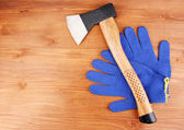 Axe and gloves on wooden background — Stock Photo