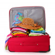 Open red suitcase with clothing isolated on a white — Stock Photo #10598248