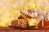 Two jars of honey,honeycombs and wooden drizzler on table on yellow background — Stock Photo