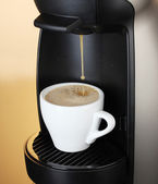 Espresso machine pouring coffee in cup on brown background — Stock Photo