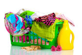 Clothes with detergent and in green plastic basket isolated on white — Stock Photo