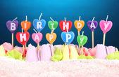 Bolo de aniversário com velas em fundo azul — Foto Stock