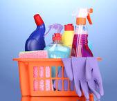 Cesta con limpieza artículos sobre fondo azul — Foto de Stock