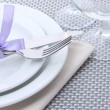 White empty plates, fork and knife tied with a ribbon and glasses on a grey tablecloth — Stock Photo