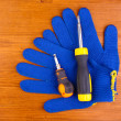 Screwdrivers and gloves on wooden background — Stock Photo