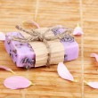 Hand-made lavender soap on wooden mat - Stock Photo