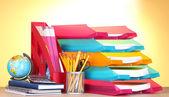 Bandejas de papel brillante y papelería en mesa de madera sobre fondo amarillo — Foto de Stock