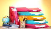 Světlé zásobníků a papírnictví na dřevěný stůl na žlutém podkladu — Stock fotografie