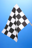 Checkered finish flag on blue background — Foto Stock