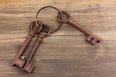 A bunch of antique keys on wooden background — Stock Photo