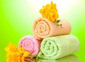 Красочные полотенца и цветы на зеленом фоне желтый — Стоковое фото