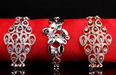 Three elegant bracelets on the red cloth on black background — Стоковое фото