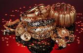 Beaux bijoux or sur fond rouge — Photo