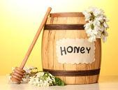 Süßer honig in lauf mit akazie blumen auf holztisch auf gelbem grund — Stockfoto
