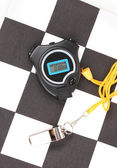 Checkered finish flag with whistle and stopwatch close-up — Stock Photo