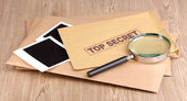 Envelopes with top secret stamp with photo papers and magnifying glass on wooden background — Stock Photo