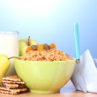 Tasty cornflakes in green bowl and glass of milk on wooden table on blue background — Stock Photo #10611040