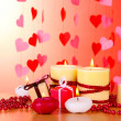 Beautiful candles with romantic decor on a wooden table on a red background — Stock Photo #10611056