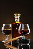 Bottle and glasss of brandy and cigar on brown background — Stock Photo