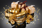 Beautiful golden jewelry and gifts on grey background — Stock Photo