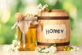 Sweet honey in barrel and jar with acacia flowers on wooden table on green background — Stock Photo