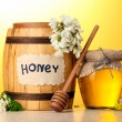 Sweet honey in barrel and jar with acacia flowers on wooden table on yellow background - Stock Photo